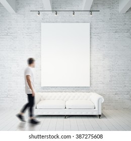 Photo of man in gallery. Waching empty canvas hanging on the brick wall and vintage classic sofa wood floor. Square, blank mockup. Motion blur