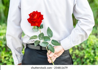 Photo of man holding a red rose behind his back  for his woman