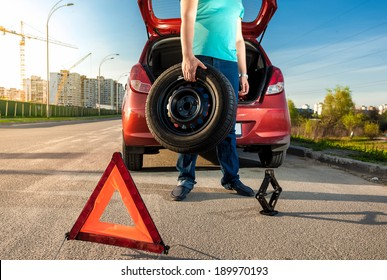 Photo of man holding spare wheel against broken car