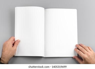 Foto. Der Mensch hält eine Zeitschrift. Für Grafikdesigner Präsentationen und Portfolios. Mock up of leere magazine. Leeres Buch einzeln auf grauem Hintergrund.