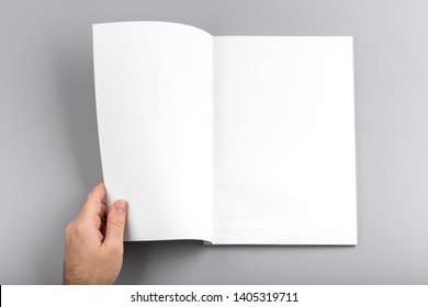 Photo. Man holds open journal. For graphic designers presentations and portfolios. Mock up of empty magazine. Blank book mockup isolated on gray background.