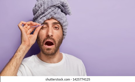 Photo of man plucks epilates eyebrows with pince, opens mouth, feels pain, has beauty treatments after taking shower, stands against purple background with towel on head. Eyebrow correction.