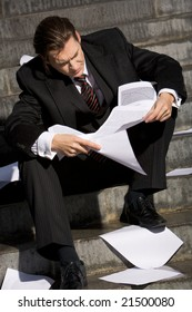 Photo of man reading documents with pensive expression while sitting on staircase