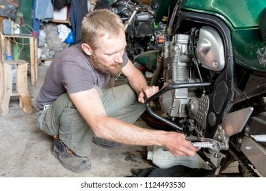 Photo man repairing the motorcycle in the garage, close-up