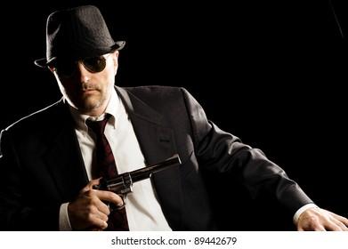 Photo of man shot with studio lighting, holding a handgun, with Fedora Hat, Dark Suit and Sun Glasses.