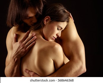 Photo of a man and woman in love and holding each other over a dark background.
