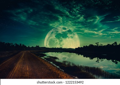 Photo Manipulation. Beautiful night sky with many stars. Landscape of green sky with super moon above silhouettes of trees. Serenity nature background. The moon taken with my camera.