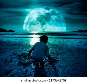 Photo Manipulation. Landscape of night sky with super moon. Back view of young girl playing sand and looking for sea animals on beach. Concept of connecting children with nature. Travel on vacation.