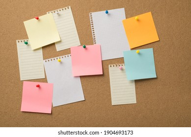 Photo of lot many colorful stickers and paper from copybooks attached to the wooden board with colorful pins
