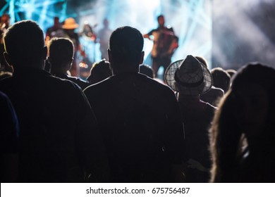 Photo of many people enjoying rock concert, audience applauding to musician band, night entertainment, music festival, happy youth, luxury party