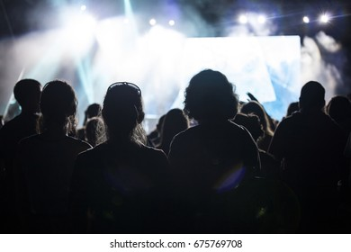 Photo of many people enjoying rock concert, crowd with raised up hands dancing in nightclub, night entertainment, music festival