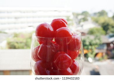 A photo of maraschino cherries in champagne glass on natural background, close up