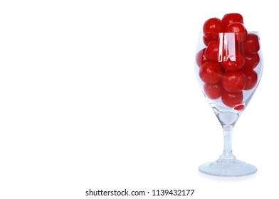 A photo of Maraschino cherries on a champagne glass isolated on white background, close up