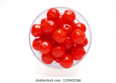 A photo of Maraschino cherries on a glass bowl isolated on white background, close up