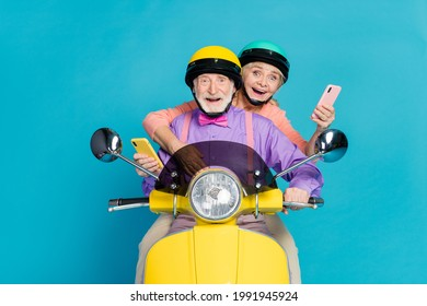 Photo of married old grey haired couple biker ride wear helmet hold phone isolated on blue color background - Shutterstock ID 1991945924