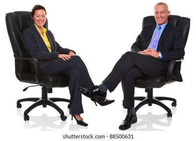 Photo of a mature businessman and businesswoman both sat in a leather executive chairs with their legs crossed and smiling to camera, isolated on a white background with natural chair relection.