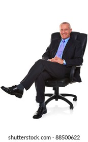 Photo of a mature businessman wearing a smart suit and tie, sat in a leather executive chair with his legs crossed and smiling to camera, isolated on a white background with natural chair reflection.