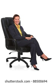 Photo of a mature businesswoman wearing a smart trouser suit, sat in a leather executive chair with her legs crossed and smiling, isolated on a white background with natural chair reflection.