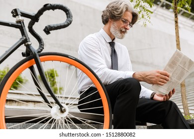 Photo of mature confident businessman in eyeglasses reading newspaper while sitting on bench with bicycle outdoors