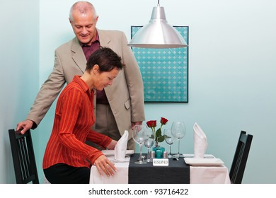 Photo of a mature couple arriving and sitting down at their reserved table in a restaurant