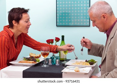 Photo of a mature couple dining in a restaurant, she is trying his pasta dish.