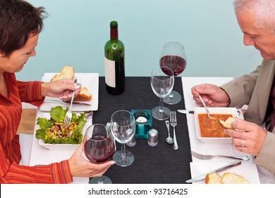 Photo of a mature couple eating starters in a restaurant, she has a bean salad and he has soup. Shot from above.