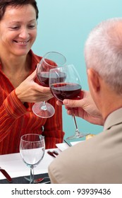 Photo of a mature couple in a restaurant toasting their glasses of red wine,