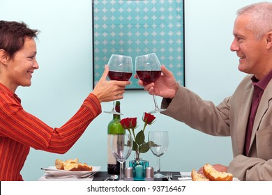 Photo of a mature couple toasting their glasses of red wine whilst sat in a restaurant