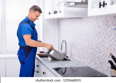 Photo Of Mature Male Workman Fixing Kitchen Sink