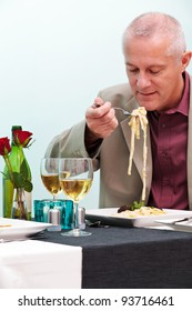 Photo of a mature man eating pasta in a restaurant.