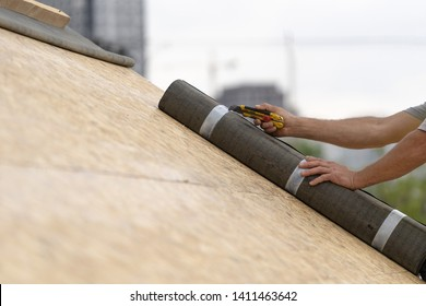 Photo of mature and professional worker on rooftop of new modern building construction. Man using special knife and unpack roll with special waterproof bitumen membrane on plywood wooden roof