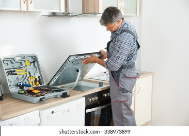 Photo Of mature repairman examining stove in kitchen