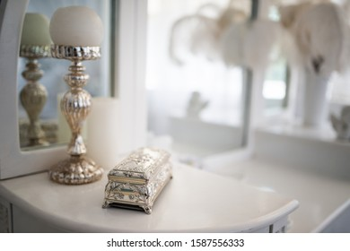 Photo of a metal casket with ornament jewelry on a defocused background.