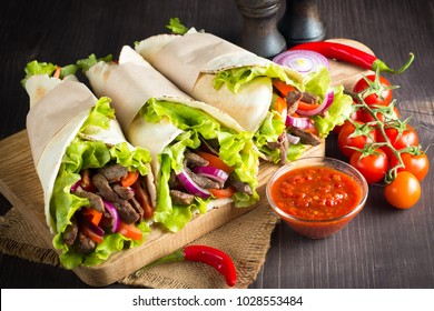 Photo of Mexican sandwich food, burrito, fajita, tacos, wrap made of tortilla, beef, chicken, fresh vegetables on rustic wooden background. Fast food concept. Healthy lunch snack. Copy space.