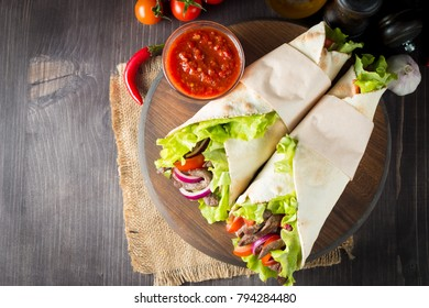 Photo of Mexican sandwich food, burrito, fajita, wrap made of tortilla, beef, chicken, fresh vegetables on rustic wooden background. Fast food concept. Healthy lunch snack. Copy space.