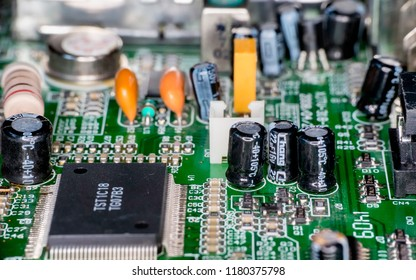 Photo of microchip in electronic device, contain big resistor, microchip and capacitor on green printed circuit board