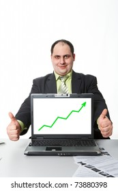 Photo of middle aged employer showing thumbs up with rising graph on laptop screen