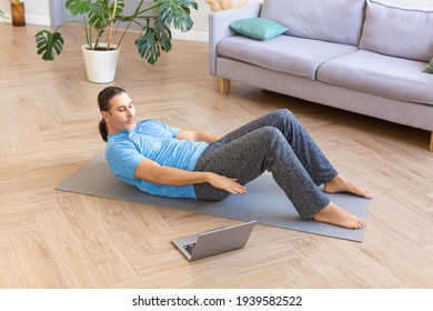 Photo of a middle aged man practicing abs crunches, training abdominal muscles on the floor while watching fitness video online on laptop.