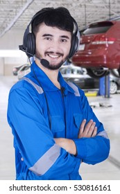 Photo of middle eastern mechanic standing in the workshop while using headset and wearing uniform