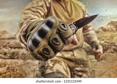 Photo of a military equipped soldier posing and holding a small tactical knife in gloves on desert battlefield background.