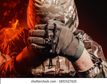 Photo of a military soldier in uniform and armor helmet sitting and holding cross religious necklace on back background with red fire burning glow.