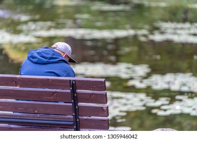 Photo of Millennial with Purple Hoodie and Grey Hat Sitting on Bench in Park, Spending Some Quality Leisure Time By the Pond on Countryside - Concept of Educated Generation Member, Free Space for Text