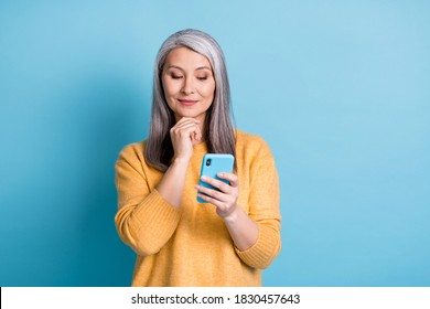 Photo of minded old woman use smartphone think thoughts decide texting typing social media chatting wear style stylish jumper isolated over blue color background