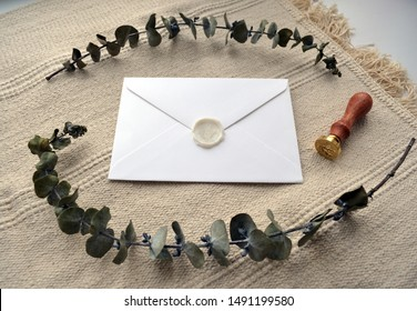 Photo mock up composition with letter, sealing wax stamp and dry eucalyptus on cotton rug. Elegant rustic floral wreath in soft beige and green color. For social media, blog, stationery presentation
