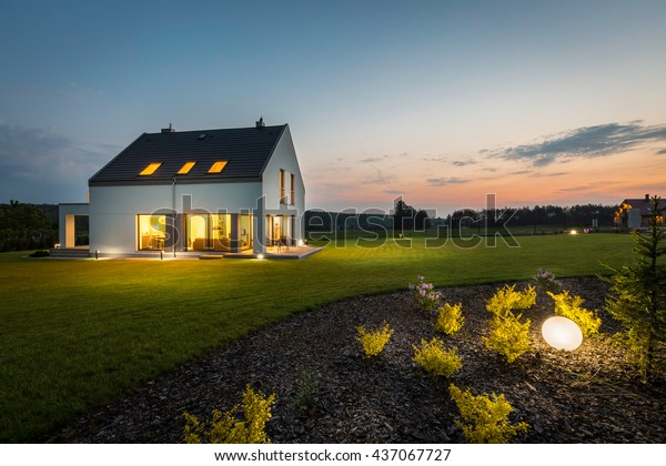 Photo of modern house with outdoor lighting, at night, external view