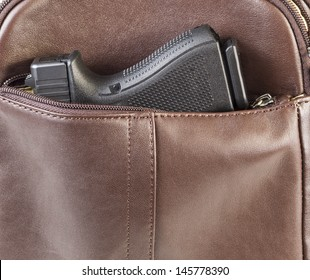 Photo of modern personal weapon in woman brown leather handbag