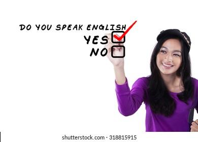 Photo of modern teenage girl learns english language and write Do You Speak English? on the whiteboard