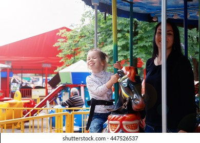 photo of Mom and daughter in the park and ride on the carousel