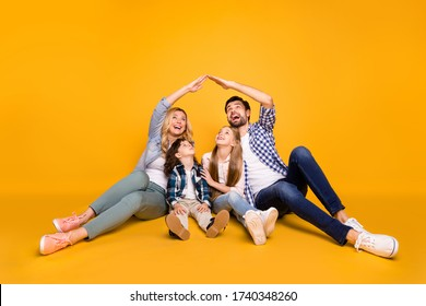 Photo mommy daddy school girl daughter small son boy happy together four member family safety care concept making hands roof above their head isolated yellow color background