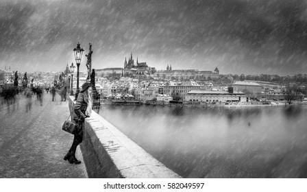 Photo montage of woman standing in black hat and winter clothing at edge of bridge in snowstorm. On behind her are blurry people. In background is historic center of city with cathedral and castle.
